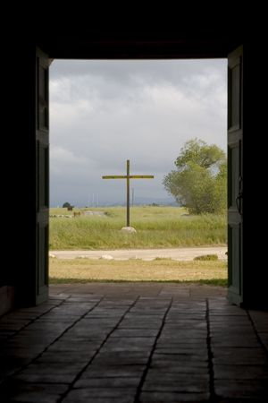 A cross as viewed through the doorway of an old California mission.