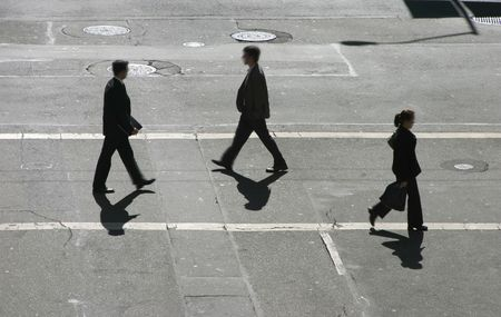 Three business people pass in the cross walk.