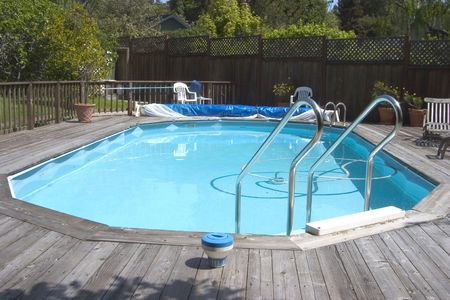 An above ground Doughboy swimming pool surrounded by decking.  photo