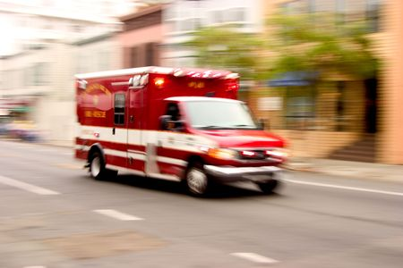 A fire rescue vehicle blazes by, its sirens whaling.  An intensional zoom blur gives a feeling of a rushed tension to the scene.