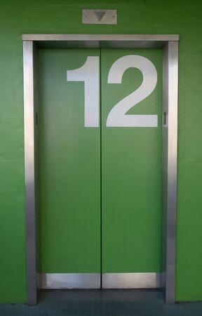 A green elevator with the number twelve painted on it - Going up or down? Banco de Imagens