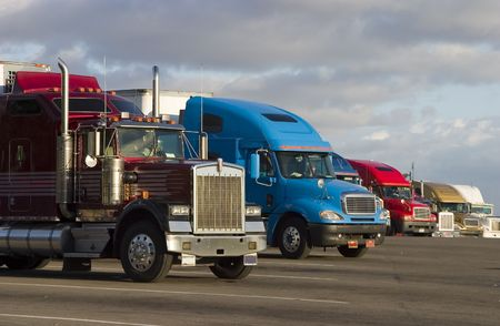 shipper: Tractor-trailer trucks in a line at a rest stop Stock Photo