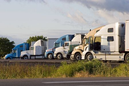 Tractor-trailer trucks in a line at a rest stop Imagens