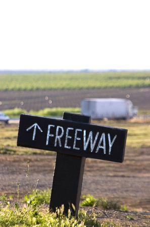 Een bordje wijst de weg naar de snelweg, die kan worden gezien in de verte.