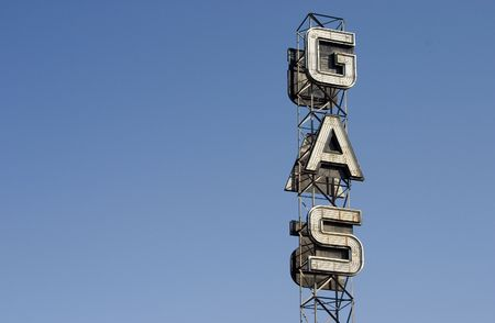 petrolium: An industrial looking sign for a gas station against the blue sky.