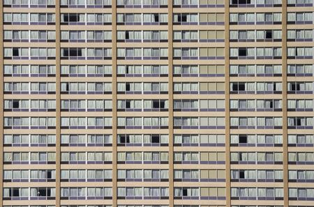 A section of a very monotonous apartment building. Many windows with curtains can be seen.  Imagens