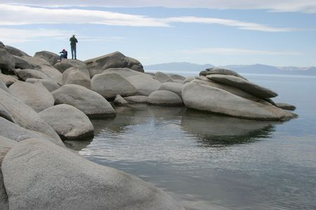 A father and son enjoy climbing on the rocks at the edge of a beautifull mountain lake. Stock Photo
