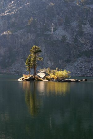 A small island in the middle of a mountain lake.  Stock fotó