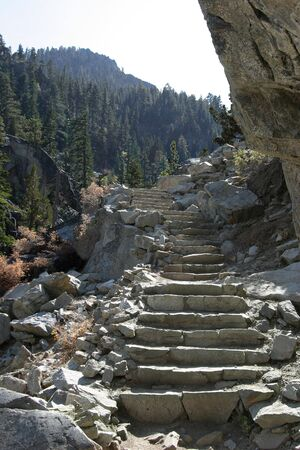 Steps cut from stones lead up a mountain trail.