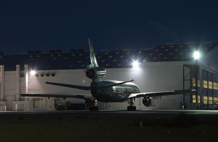 class maintenance: A jet airplane parked near its maintenance hangar. All visible airline markings have been removed.