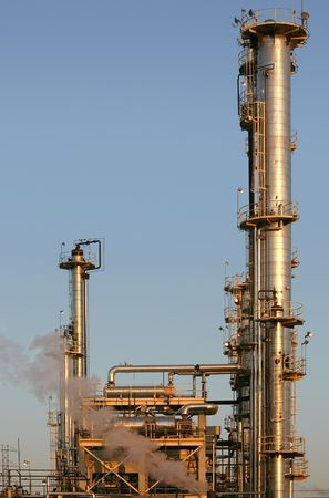 smokestacks: The towers and piples of an oil refinery.