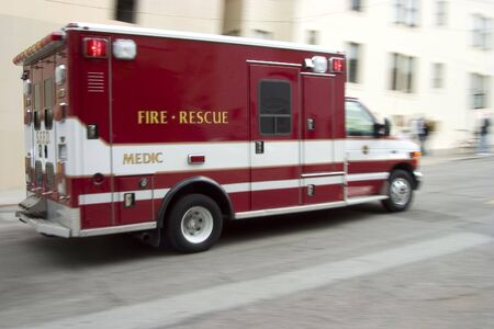 blazes: An ambulance blazes by, its sirens whaling.  An intensional camera blur gives a feeling of a rushed tension to the scene.