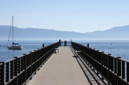 A pier extends into a beautiful mountain lake.