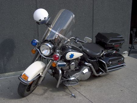 A fancy police motorcycle sits parked on the sidewalk.