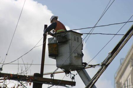An electrician, high on a lift, works the wires.  Zdjęcie Seryjne