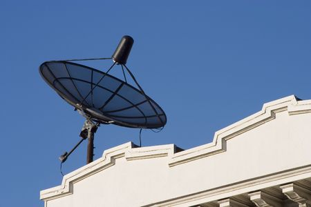 A rooftop dish pulls in information from a satellite.