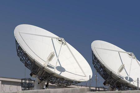 Two satellite dishes point skyward.