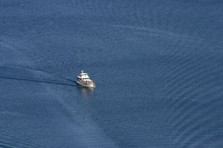 A birds-eye view of a yacht on a large patch of blue water.