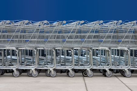 consume: A line of shopping carts against a blue wall.