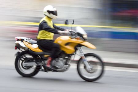 intentional: A speeding motorcycle with intentional camera motion blur. Stock Photo