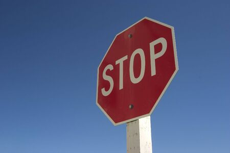 authoritative: A authoritatively low angle view of stop sign against a very blue sky.