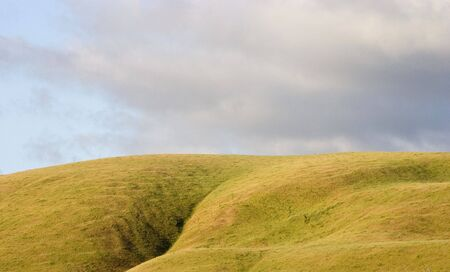 encroach: Dark clouds encroach on a sunny rolling hills. Stock Photo