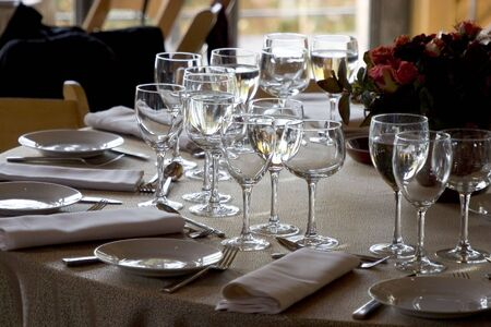 forground: A fancy table setting awaits the guests.  Focus is on the forground plate and glasses.