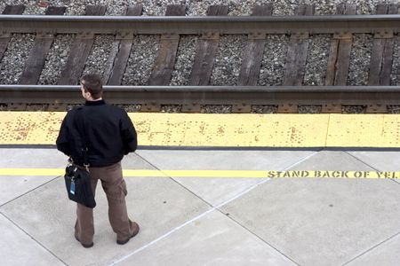 A man awaits the train for his morning commute to work.