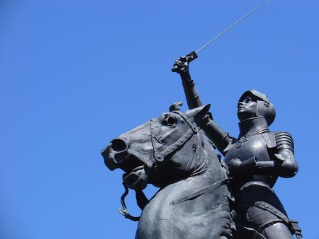 An old park statue from the late 1800s holds  up a sword up in an apparent show of victory.  The statue depicts a female Reklamní fotografie