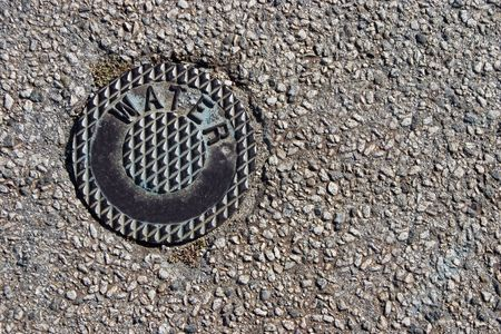 A metal cover on the street, protecting a water department valve.