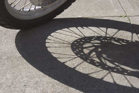 The wheel of a motorcycle casts a shadow on the sidewalk.
