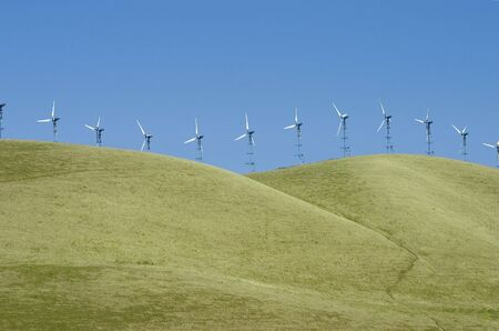 A line of windmills on rolling hills in California.  Banco de Imagens