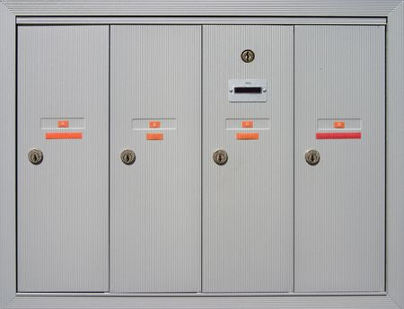 recieve: A group of mailboxes doors outside of an apartment building.