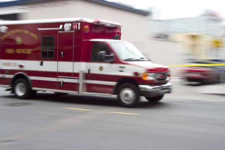 An ambulance blazes by, its sirens whaling.  An intensional camera blur gives a feeling of a rushed tension to the scene. photo