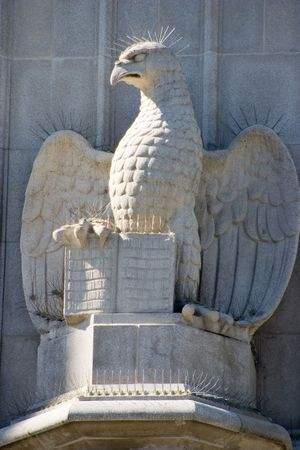 achitectural: An architectural statue on the side of an old church depicts an eagle holding open a book. Stock Photo