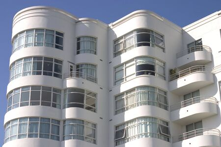 A large art deco apartment building displays its face of curved windows and balconys. Banco de Imagens