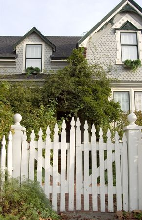 Picket fence entry gate leads to an overgrown front yard of an old house. 免版税图像