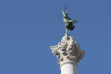 A female victory statue, atop a column, raises a trident into the air.