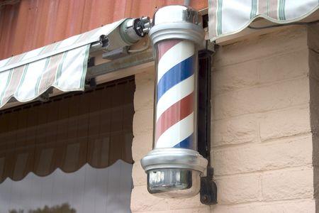 A barber pole outside of a hair salon. Stock fotó