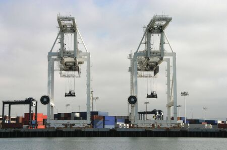 Two large cargo cranes are poised to unload another container ship.