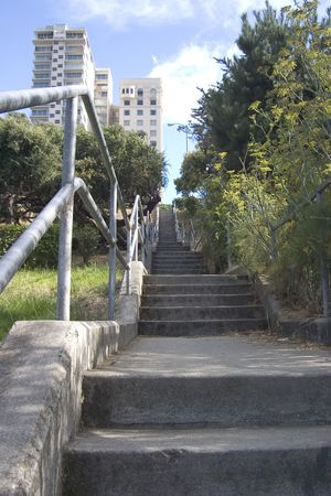 A long stairway leading up a hill to a group of city apartments.