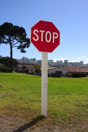 authoritative: A authoritatively low angle view of stop sign against an urban backdrop. Stock Photo