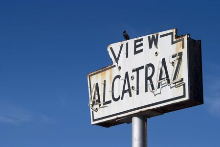 """A bird sits atop a broken old sea-side neon sign that reads """"View Alcatraz�."""