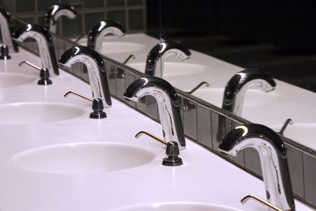 sinks: A line of sinks in a public bathroom. Stock Photo