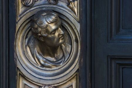 A man�s head sticking out of an old brass door.