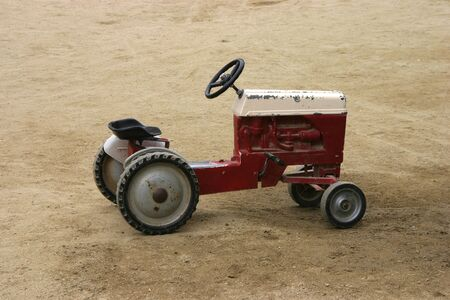 An antique toy tractor sits in a field of dirt.