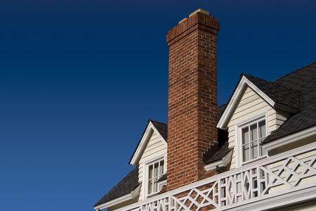 A brick chimney rises between two roof windows. Фото со стока