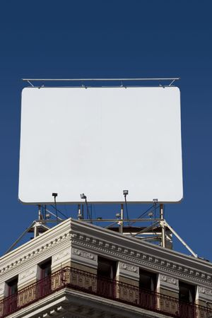 inform information: A billboard mounted on the roof of a corner building.