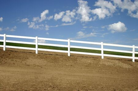A slanted fence on the edge of a farm field.