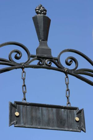 An ornate iron name plaque hangs above a gateway. 版權商用圖片